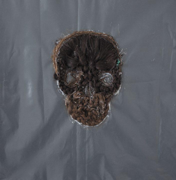 Skull 2020. human hair on rubbish bag 55 x 55 cm